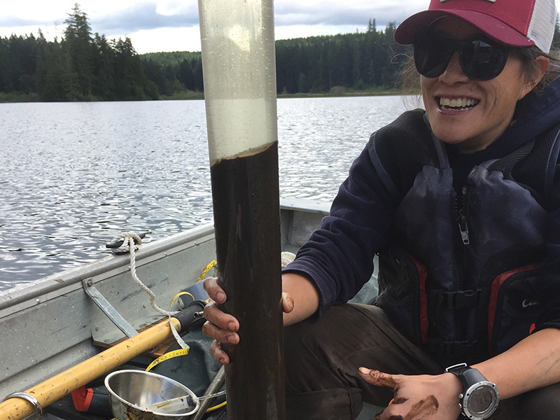 Scientist on a boat holding a plastic tube filled with mud