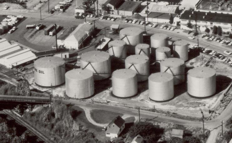 Black and white aerial view of fourteen large above ground storage tanks in an industrial area.