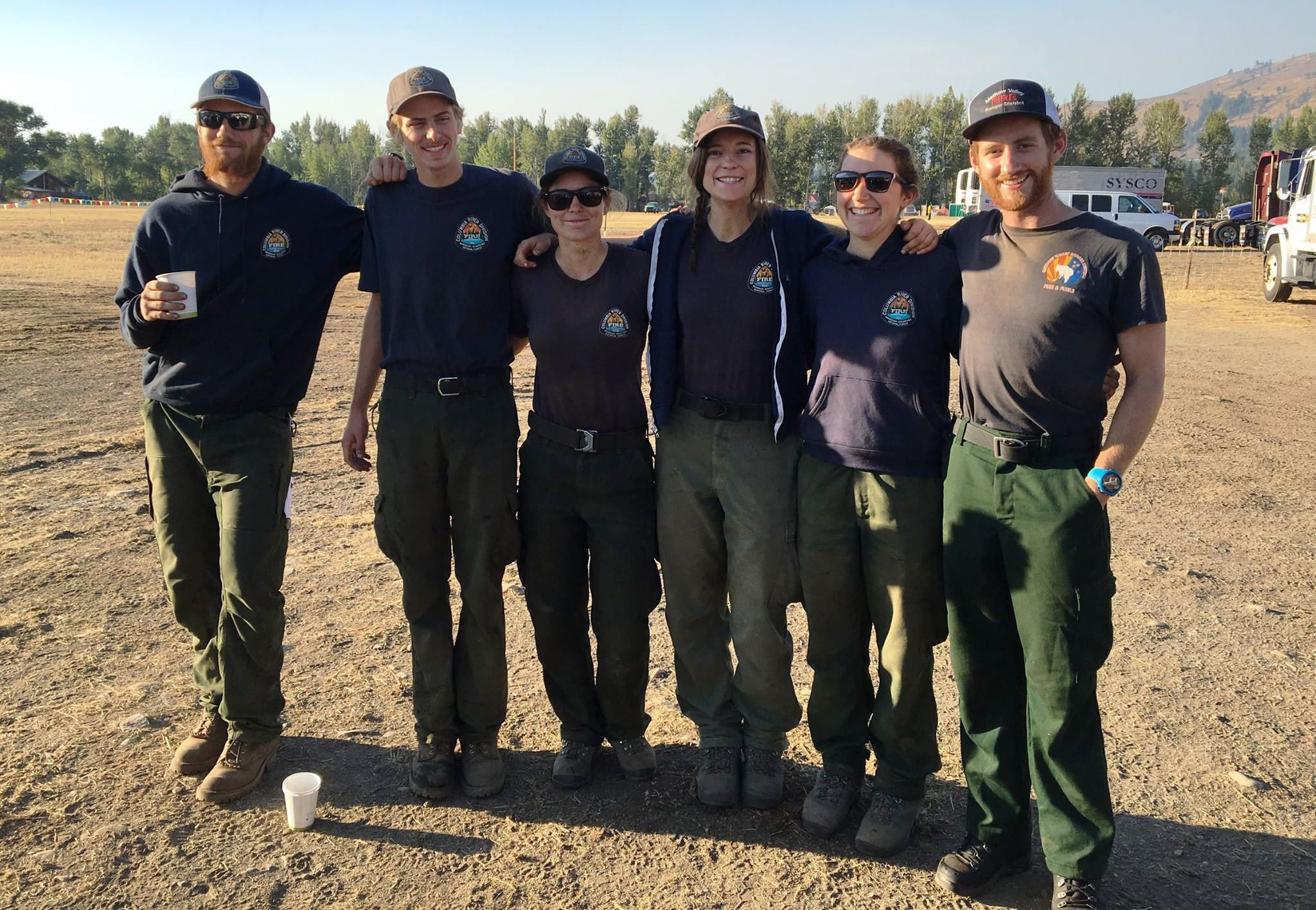A group of six firefighters gather for a photo in an outdoor field, wearing dark green pants and dark blue uniforms.