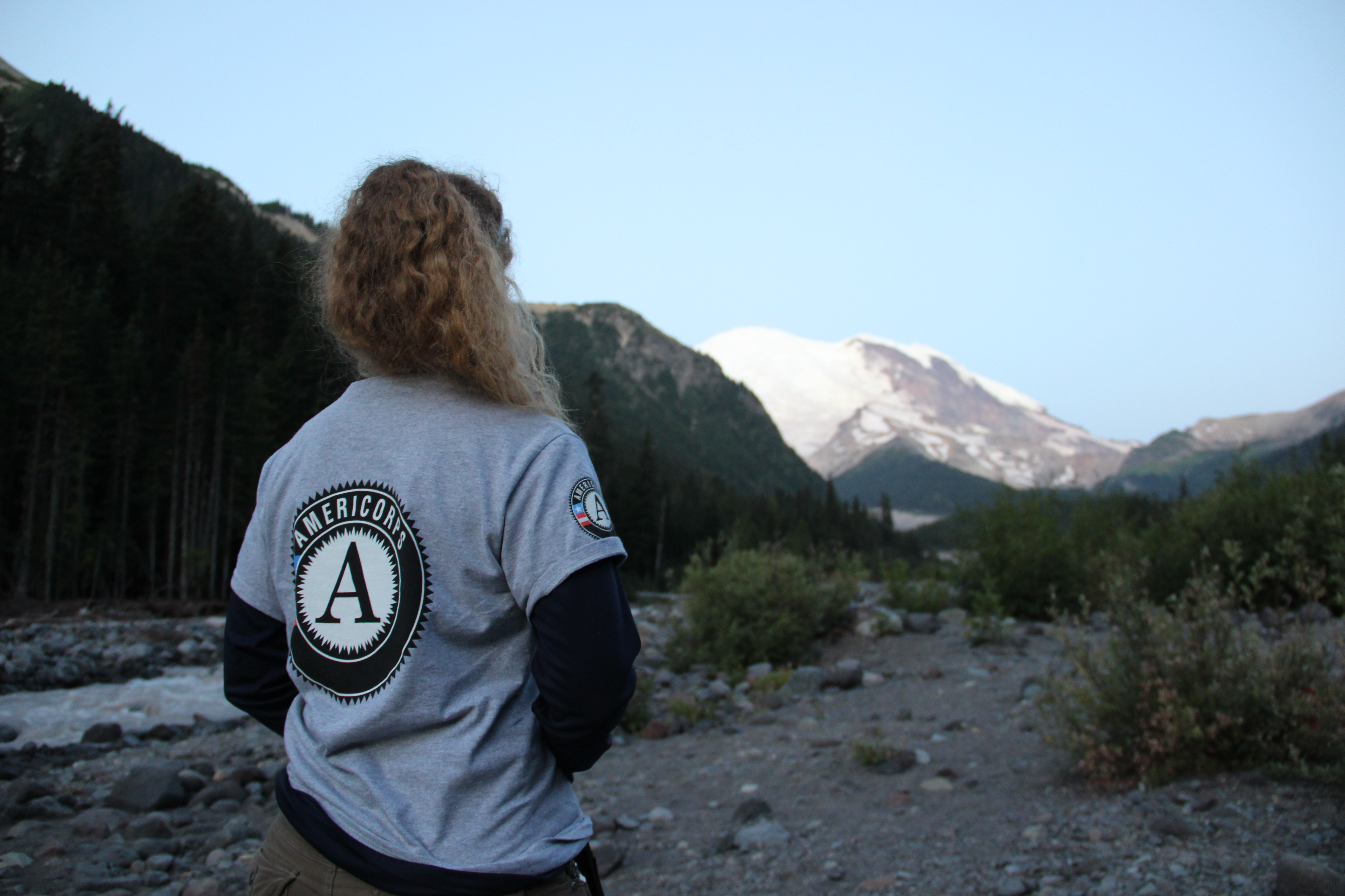 A person stands in a rocky wash, wearing a tan shirt with an AmeriCorps logo looking at a mountain, at dusk