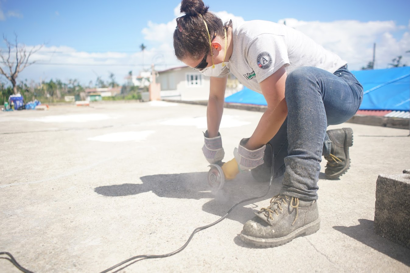 A person kneels on concrete to conduct a roof repair in a sunny climate.