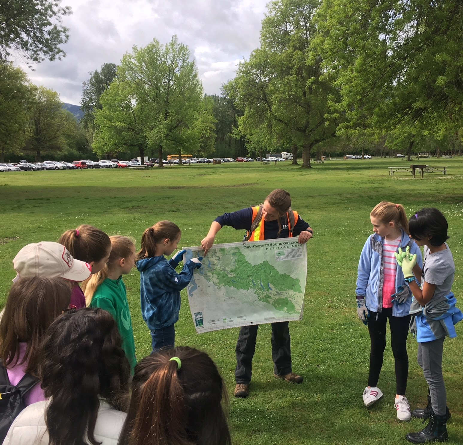 A person points to a map, showing a group of children a location, while standing in a grassy field.