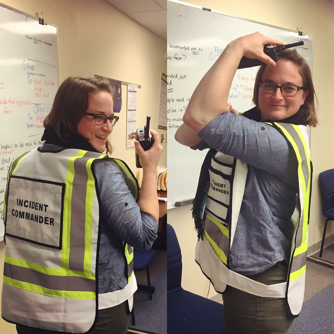 "Split photo: Nina Rubenstein holds walkie talkies on the left, and flexes her muscle on the right. She is wearing ""Incident Commander"" vest."
