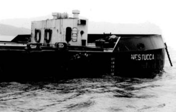 A black and white image of the Nestucca barge in water