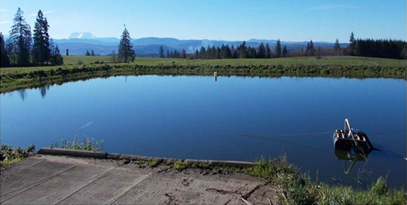 A photo of a waste containment pond with Mt. St. Helens in the background