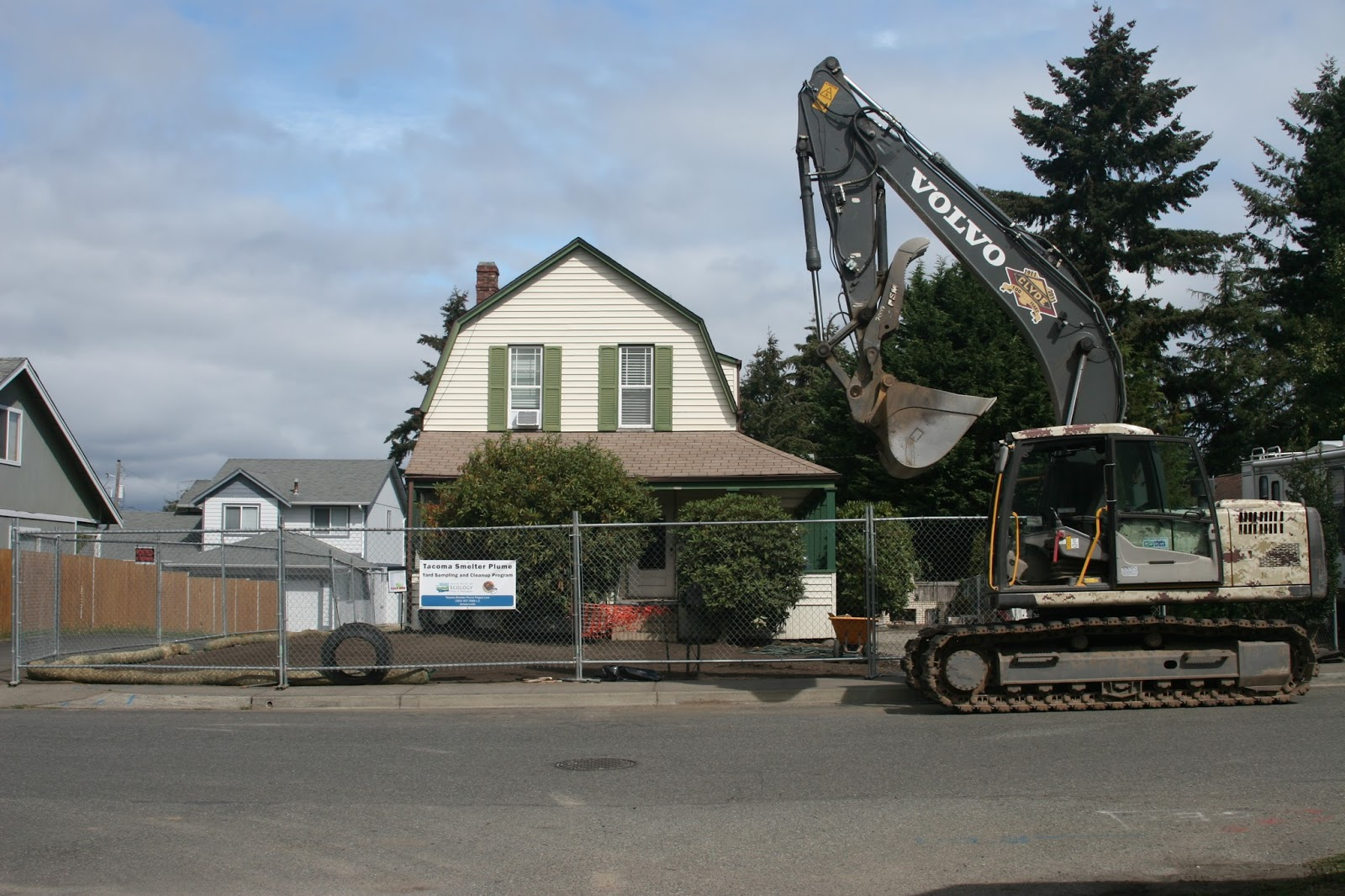 An excavator in front of a fenced-off house with a bare dirt yard.