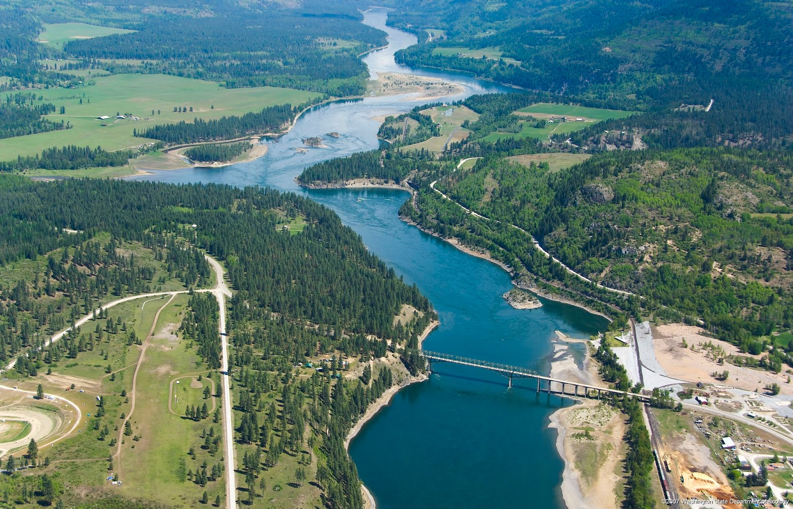Aerial view of the Columbia River, surrounding forests and a bridge crossing the river