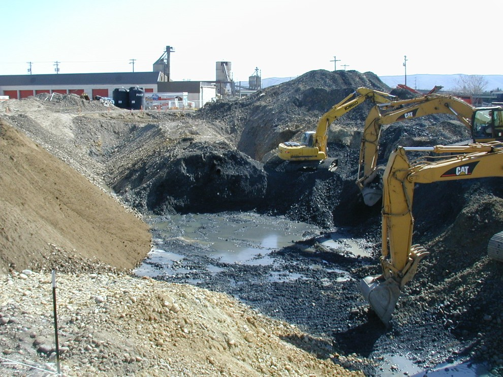 Two excavators scoop contaminated earth and gravel from a pit. Water is surfacing at the bottom of the pit ,