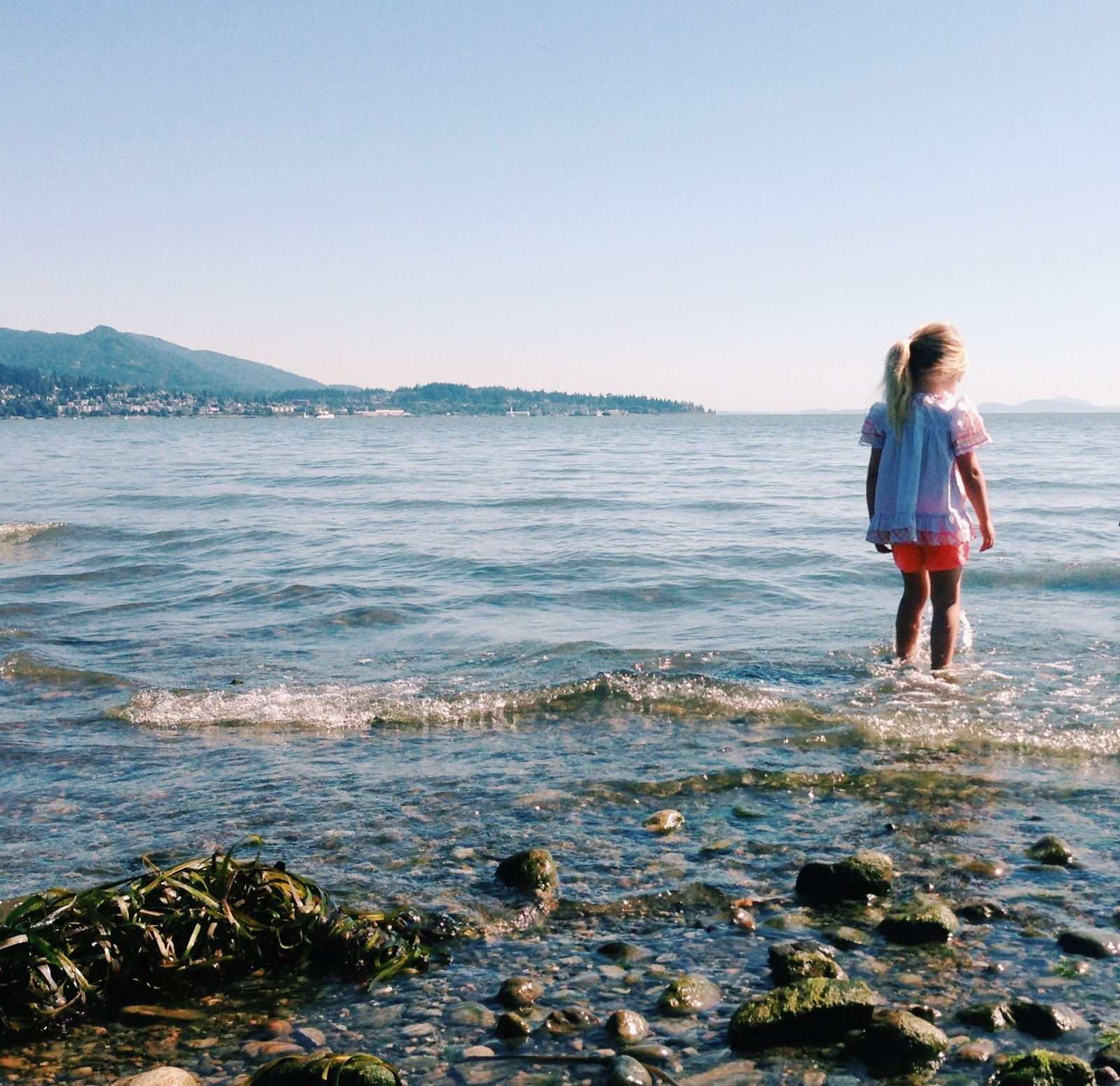 little girl wading in sound with city and mountains in the distance