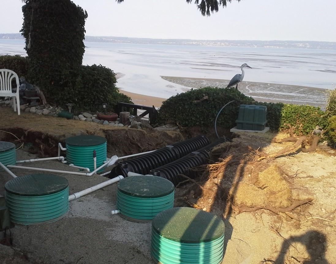 septic system with ground dug up around it and the Puget Sound in the background.