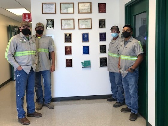 Wastewater Treatment Plant operators stank proudly next to a wall covered in awards wearing covid-19 masks