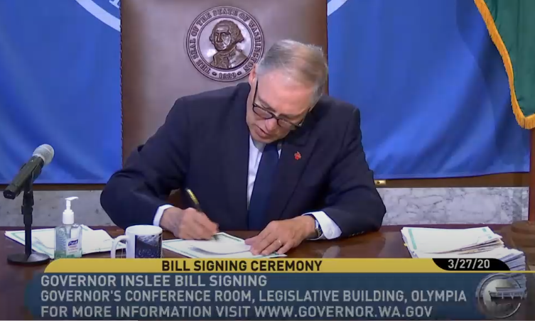 Governor Jay Inslee sitting at a desk signing a bill.