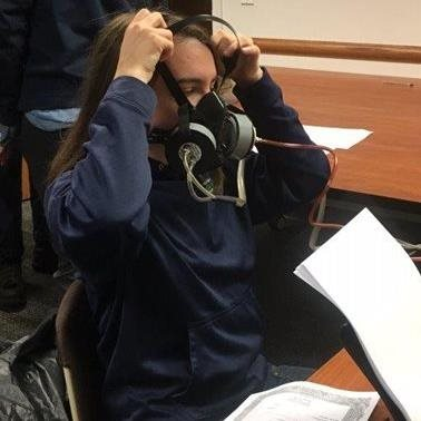 Photo of a person putting on a respirator.