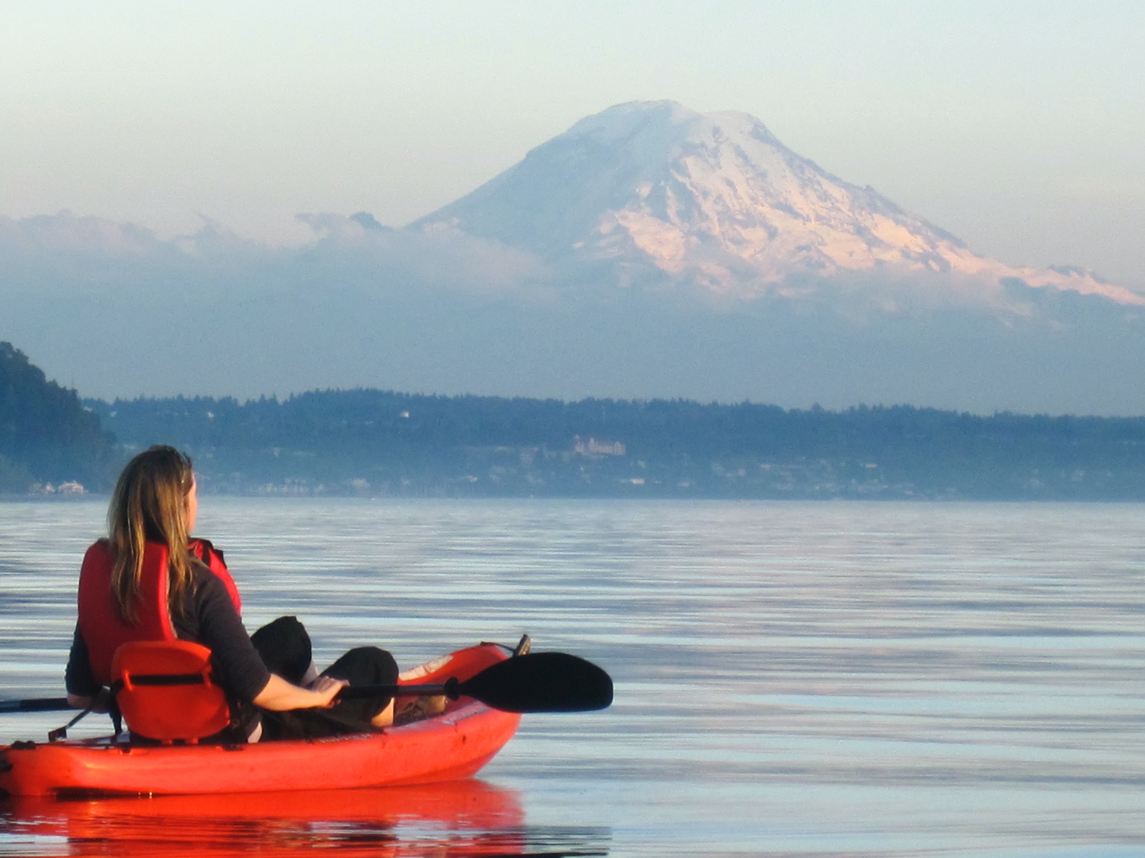 A woman kayaking on Puget Sound with Mount Rainier in the background
