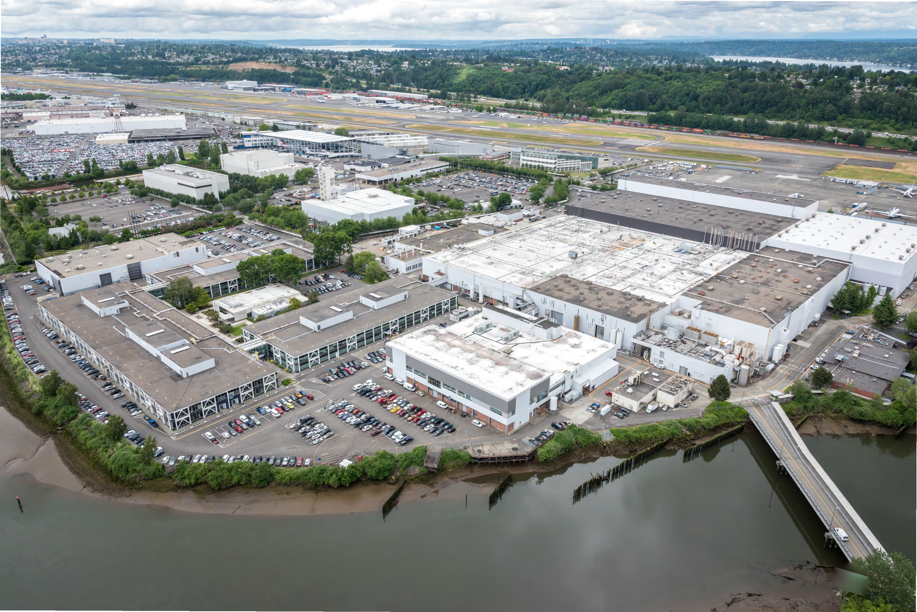 A commercial and industrial site with many buildings and parking areas. A river is seen in the foreground, and the background shows more industial buildings, an airfield and a wooded ridge with homes.