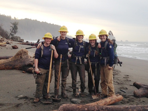 WCC work crew on a Washington beach holding tools.