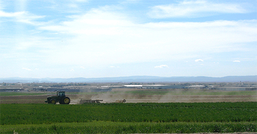 Tractor working in a field with the town of Quincy in background.