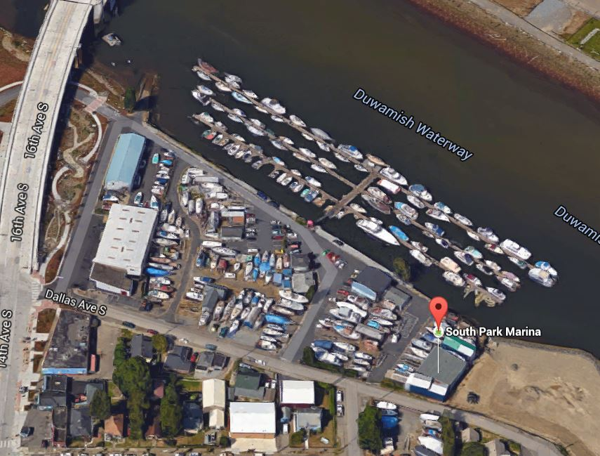 Aerial view of a riverfront marina with three T piers, plus and upland dry moorage area with boats parked on trailers.