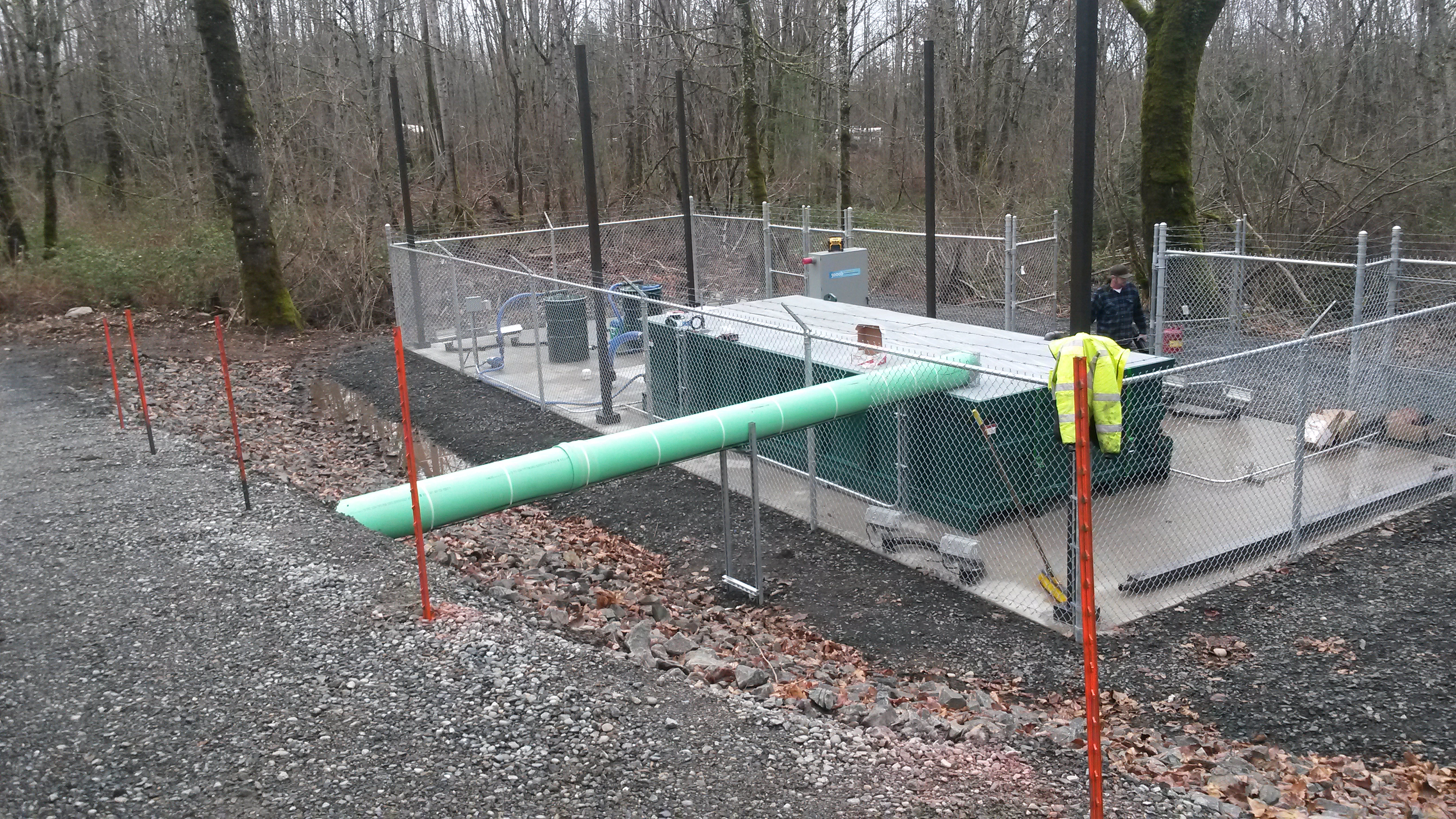 Machinery inside a fence, with a teal inflow pipe is seen on a wooded hillside.