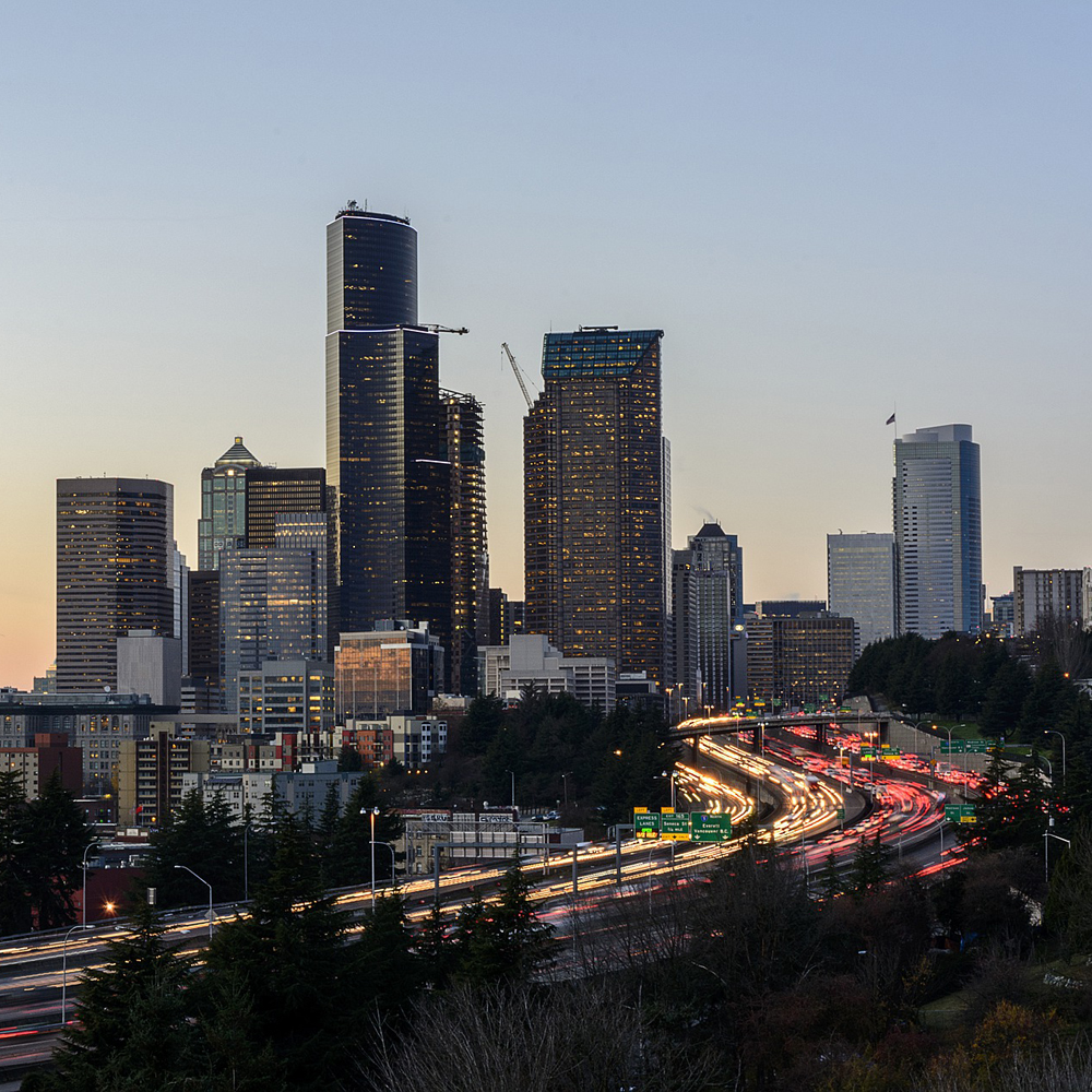 A highway of cars in front of the Seattle skyline at sunset