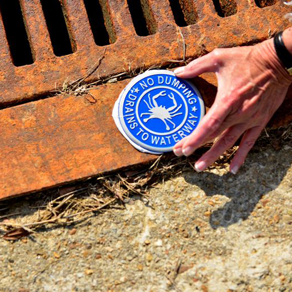 Hand placing a sign on a storm drain that reads