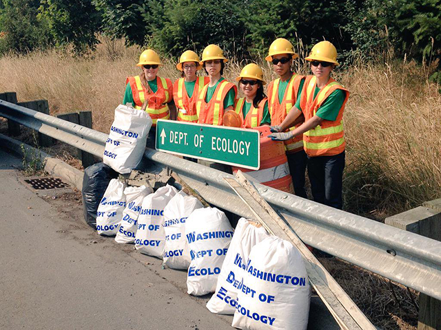 young people in safety gear standing behind a guardrail, with bags of litter lined up in front of them.
