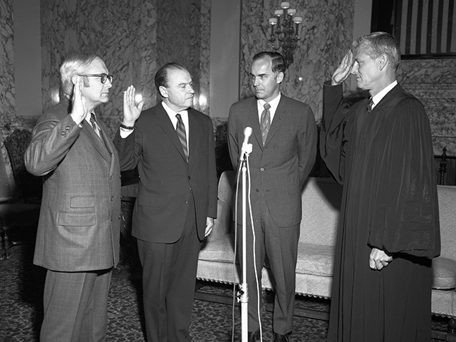 Four men at a swearing-in ceremony, one of them wearing judge's robes