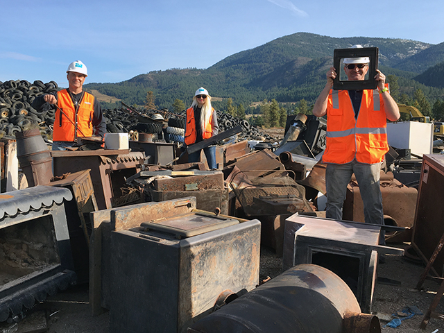 Ecology employees in safety gear, standing among a pile of old woodstoves
