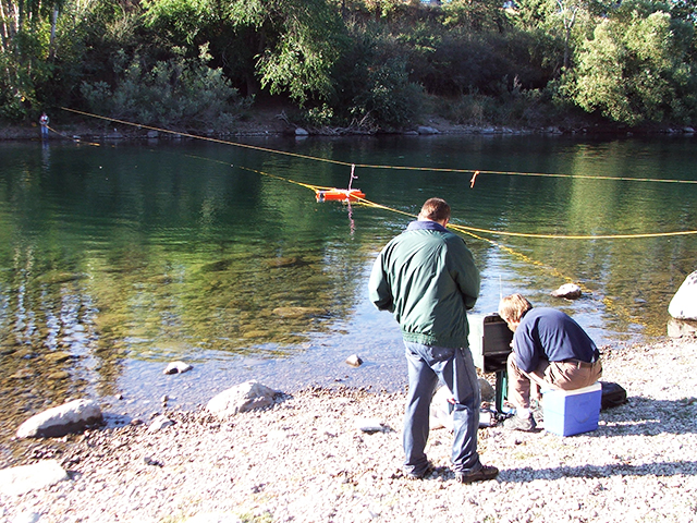 Two employees setting up monitoring equipment on the Spokane river