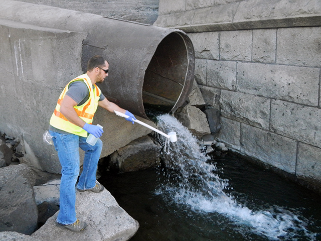 Ecology employee using a cup on the end of a stick to collect stormwater from a drainpipeto test for pollutants