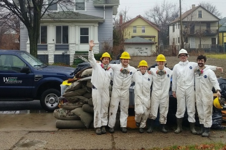 WCC AmeriCorps members stand near debris pile removed during the mucking and gutting of a home in Detroit, Michigan.