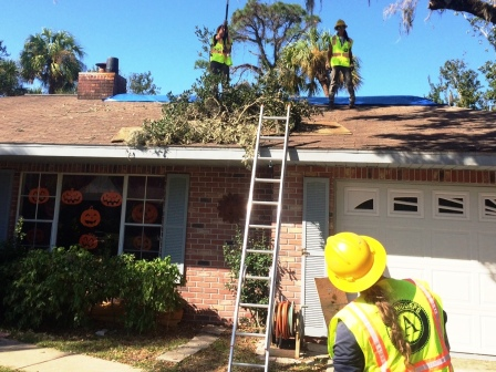 WCC AmeriCorps members remove branches threatening the roof of a Florida home.
