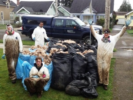 WCC AmeriCorps members pose near garbage bags full of wall insulation collected during a mold treatment operation in Grays Harbor, Washington.