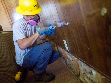 WCC AmeriCorps member checks for moisture in the walls of a home in Louisiana.