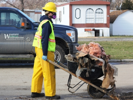 A WCC AmeriCorps member pushes a wheelbarrow full of debris pulled from a damaged structure in Missouri.