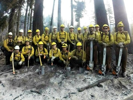 A crew of 20 WCC AmeriCorps members gather for a photo holding shovels, axes and chainsaws in a burned out area during the Stewart Mountain wildland fire response.