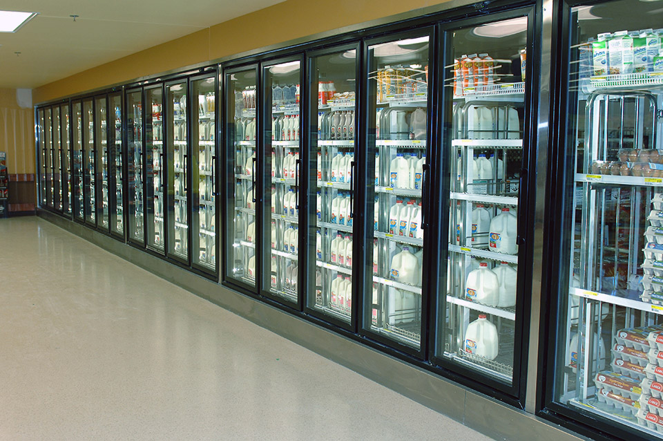 A row of commercial refrigerators in a grocery store.