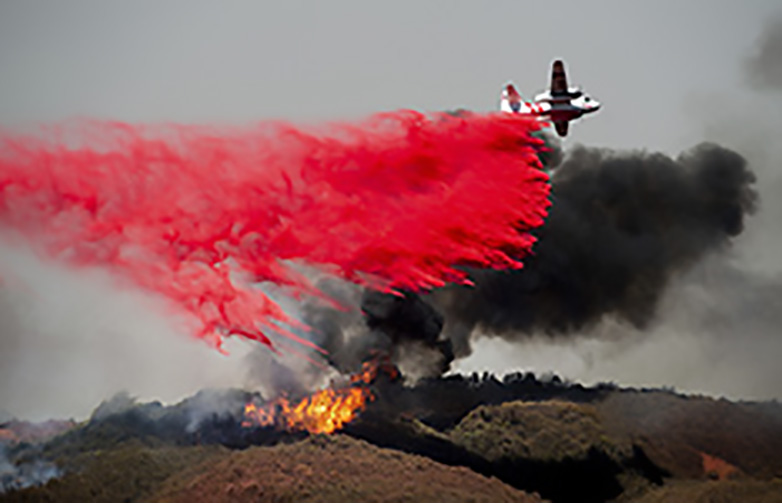 a plane dropping red fire retardant on a wildfire