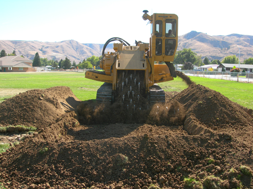 Heavy equipment removing lead- and arsenic-contaminated soil being from a playfield.