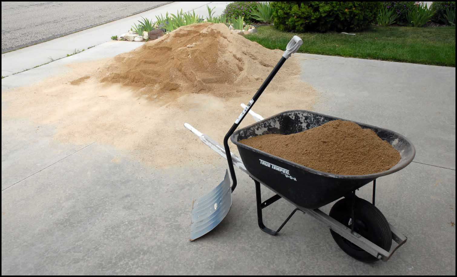 Picture of wheelbarrow full of dirt with a shovel next to it.