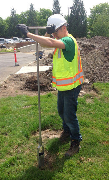 Picture of a person sampling soil with a hand auger.