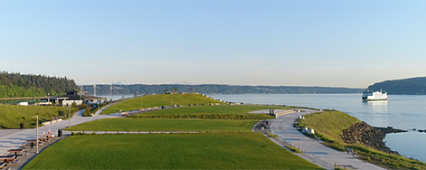 View of the new park showing walking trails, lawns, water, and ferry in the background.