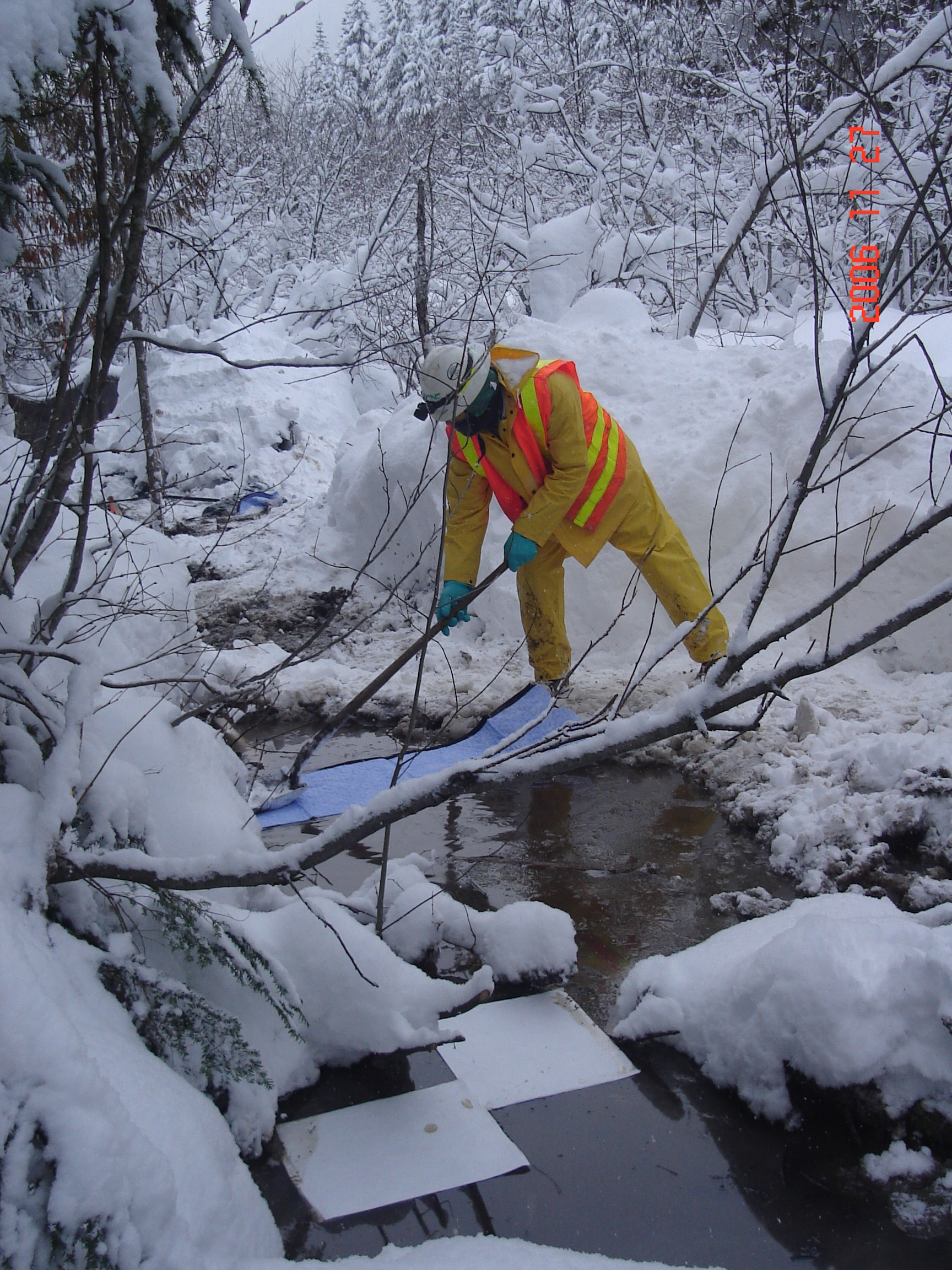 Worker placing pads to absorb diesel in a small stream that flows into Silver Creek.