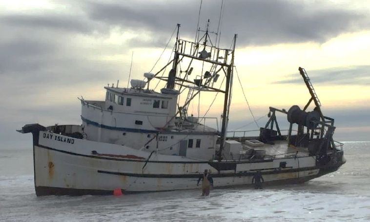 Fishing vessel DAY ISLAND aground on beach, listing to port.