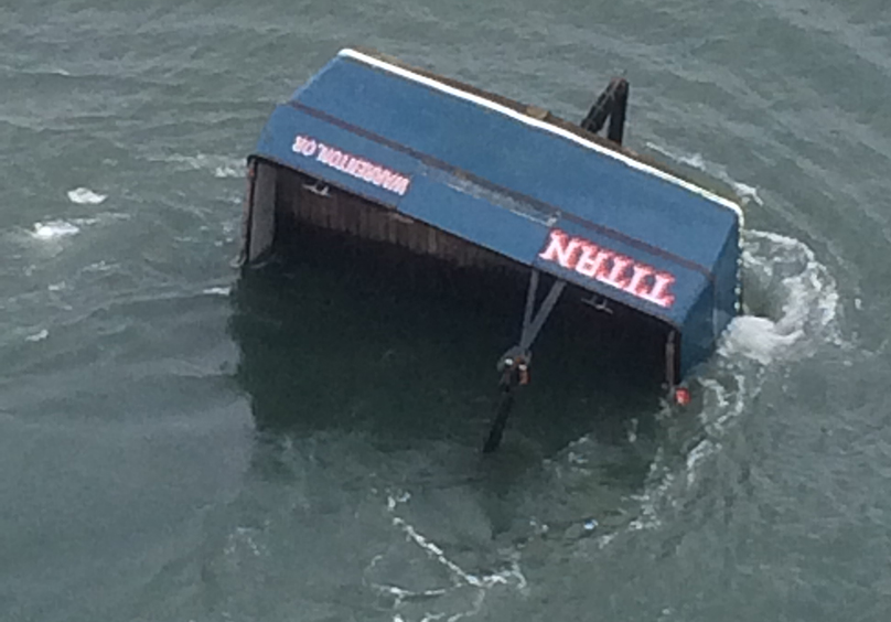 Aerial view of fishing vessel TITAN, sunk bow downward in water, with only the stern visible.