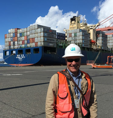 Man in a hard hat and safety vest stands in front of a container ship.