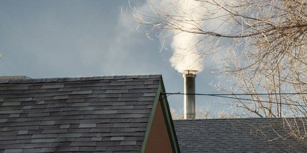 smoke coming out of metal chimney on a rooftop