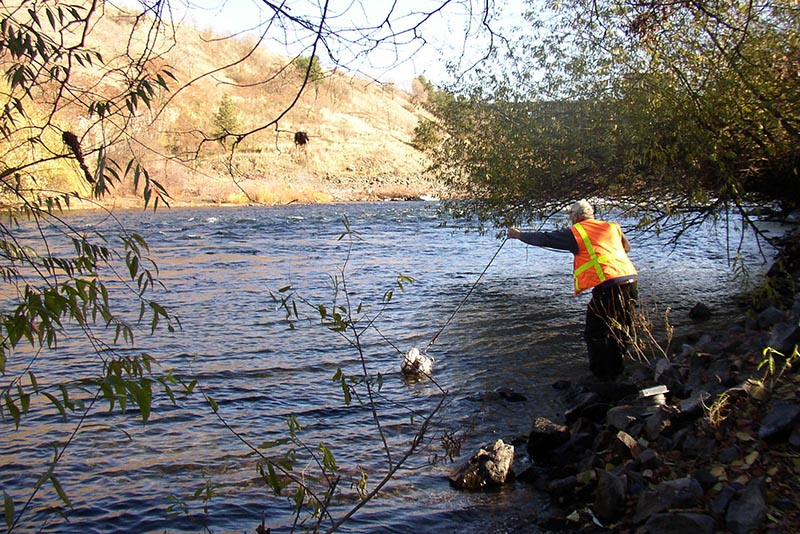 Scientist tosses a group of sample bottles on a rope into a wide river from an Eastern Washington river bank.