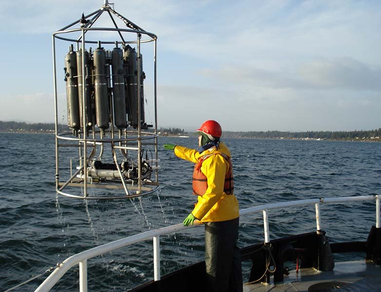 Scientist on deck of research boat directs the retrieval of a large sensor array that looks like a group of metal tanks in a frame built from stainless-steel tubing