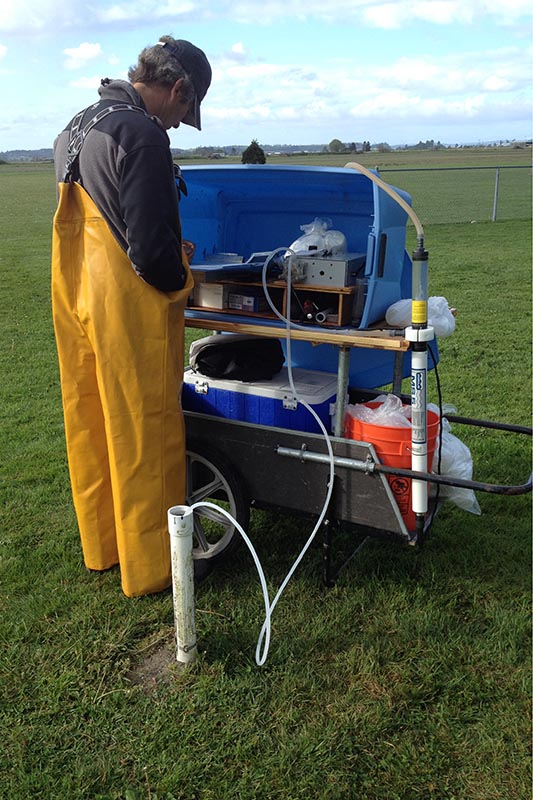 Scientist in yellow rain pants stands beside a garden cart outfitted with a pump to sample a monitoring well near a drain field. A tube runs from the cart to a white pipe in the ground.